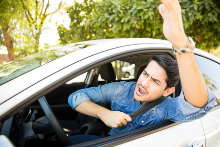 Portrait of angry young man sitting in his car shouting and gesturing at other drivers during traffic on road