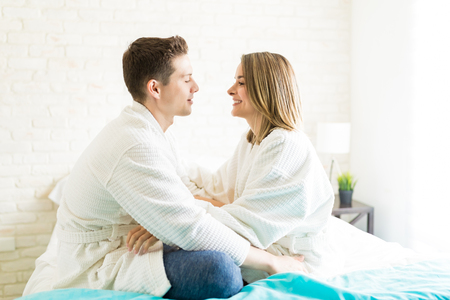 Side view of romantic couple wearing bathrobes while sitting face to face on bed at home