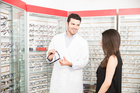 Professional young man optician helping woman client to choose a some eyeglasses