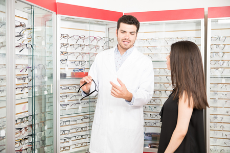 Handsome ophthalmologist helping woman to choose glasses in optical store Фото со стока