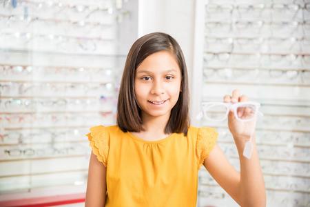 Adorable girl choosing eyeglasses frames in optical store holding white glasses Фото со стока