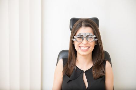 Pretty young woman enjoying eye checkup wearing trial frame looking at camera