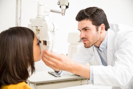 Handsome doctor using phoropter to examine girls eyes Stok Fotoğraf