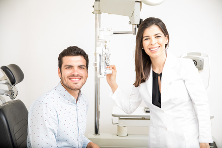 Cheerful man sitting on chair with beautiful optician standing while dong eye test using phoropter in optical laboratory