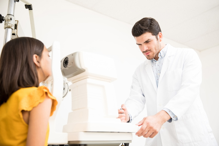 Handsome optometrist doctor examining eyesight of little girl in eye ophthalmological clinic