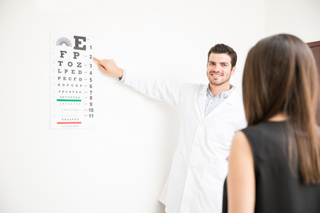 Young optician pointing numbers for patient to read for vision checkup in clinic test room Stock Photo