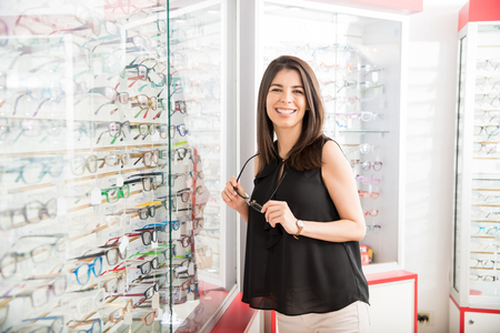 Beautiful latin woman selecting new frame for eyeglasses from optical store while smiling and looking at camera