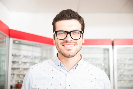 Portrait of handsome man in glasses looking at camera while standing in optician shop