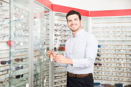 Handsome smiling man holding black frame eyeglasses for purchase standing near display rack looking at camera