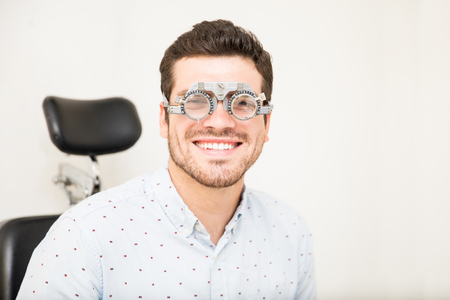 Portrait of handsome smiling man with trial lens at optician center while looking at camera