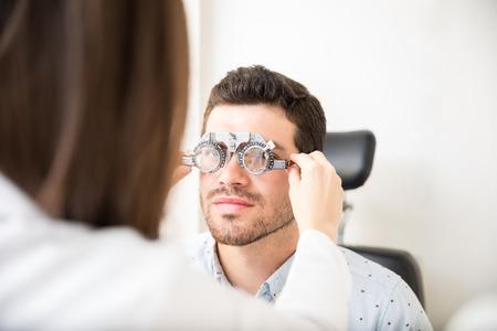 Female optician adjusting lens of trial frames on mature man