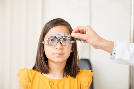 Optician hand determining prescription values with trial frame for cute school girl
