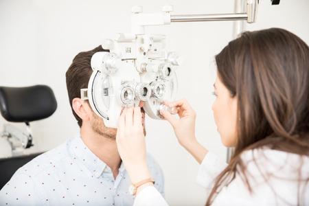 Beautiful woman optometrist performing eye checkup with phoropter at clinic Stockfoto