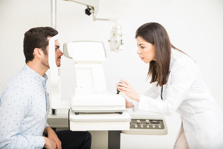 Handsome man doing eye test with woman optician using tonometer in optical store Stockfoto