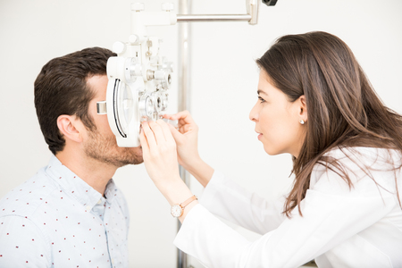 Side view of beautiful woman in doctor uniform checking man patient vision using phoropter in clinic Stockfoto