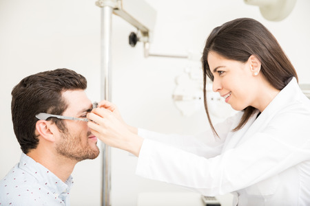 Handsome man getting eye check up done with beautiful ophthalmologist while arranging trial glasses at laboratory Stockfoto