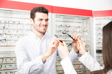 Happy customer man trying new spectacles with black frame as suggested by woman optician in optical store