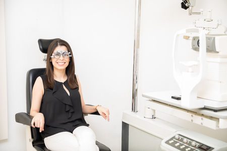 Cheerful young woman sitting in ophthalmologist clinic wearing trial frame for vision examination