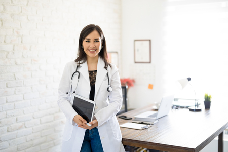 Portrait of beautiful young female doctor standing by her desk holding a digital tablet