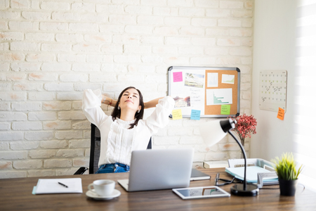 Beautiful hispanic businesswoman with eyes closed reclining in chair with her hands behind head