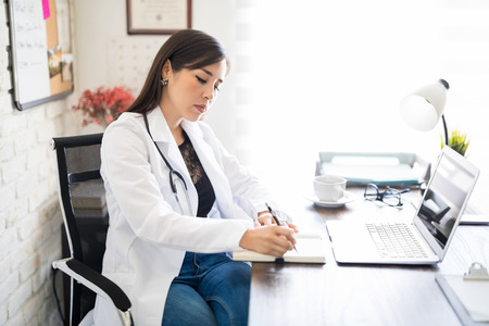 Beautiful young doctor writing a medical prescription on a book while sitting at her desk with laptop in her office