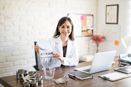 Portrait of attractive nutritionist sitting at her clinic holding weight scale with measuring spoon set and bowl on table Stock Photo