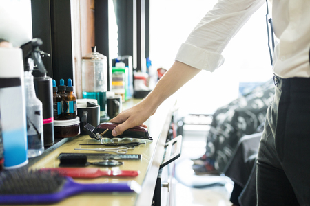 Cropped image of hair expert keeping trimmer on counter in salon