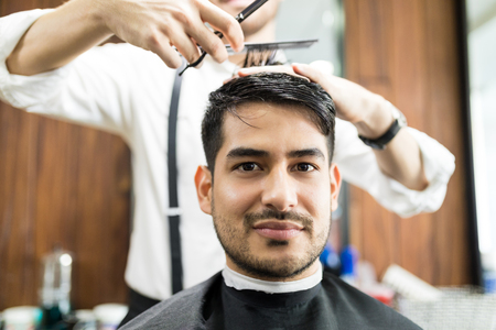 Closeup of confident young man getting hair styled by hairdresser in salon