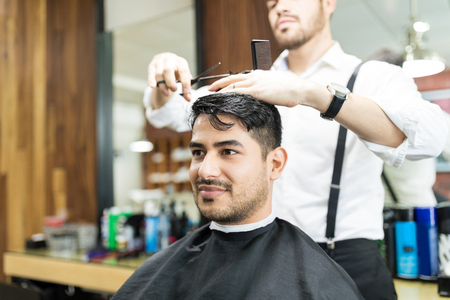 Confident young man looking away while getting haircut from barber at shop