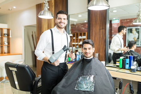 Portrait of young barber with blow dryer standing near male client for new hairstyle in salon