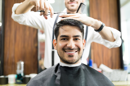 Young male client smiling while getting service from hairdresser in salon