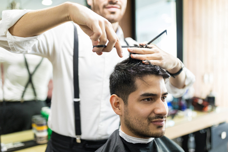 Midsection of professional barber giving haircut to male in shop