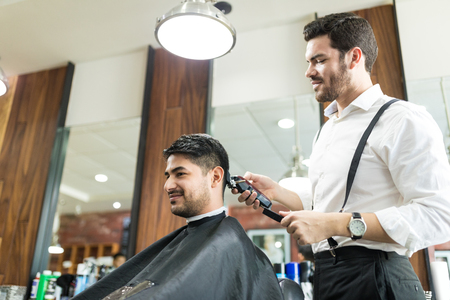 Low angle view of young professional barber trimming client's hair in salon Banque d'images
