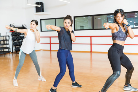 Determined women in sportswear punching the air in gym 写真素材