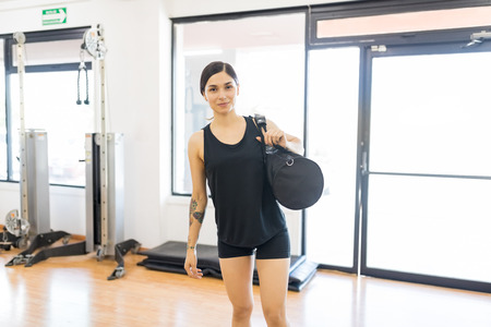 Portrait of sporty young woman with duffle bag standing in gym