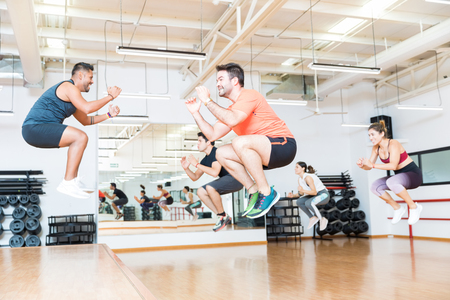 Full length of male trainer doing tuck jumps with clients in health club 写真素材 - 106186875