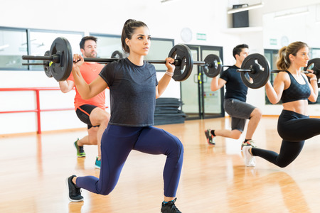 Female weightlifter lifting barbell while doing lunges with friends in health club Stock Photo
