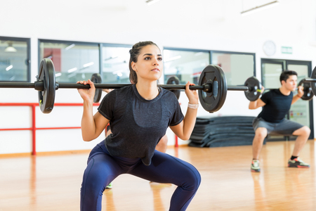 Dedicated female client exercising with barbell in health club 写真素材 - 106186913