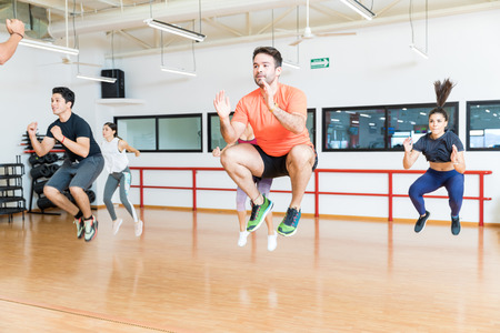 Male and female clients doing tuck jumps on hardwood floor in gym