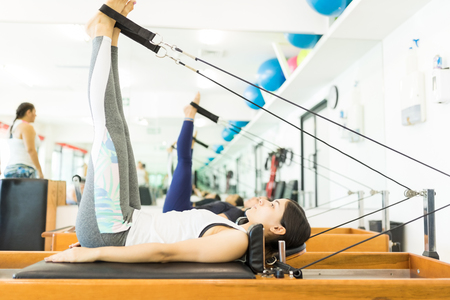Side view of female client maintaining her fitness while exercising on reformer machine in gym