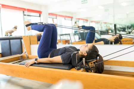 Side view of flexible female using pilates reformer machine in gym