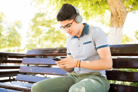 Portrait of young latin boy sitting on bench outdoors with phone and wearing headphone listening music Stock Photo