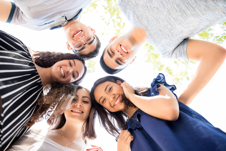 Low angle view of group of teenagers standing in a huddle with their heads touching and looking at camera