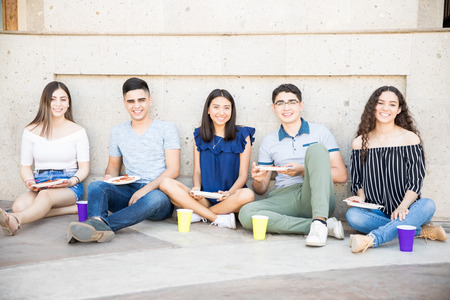 Group of five teenage boys and girls sitting outside in sidewalk eating pizza Stock Photo