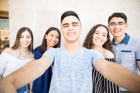 Teenage boy taking selfie with friends on smartphone while hanging out in city