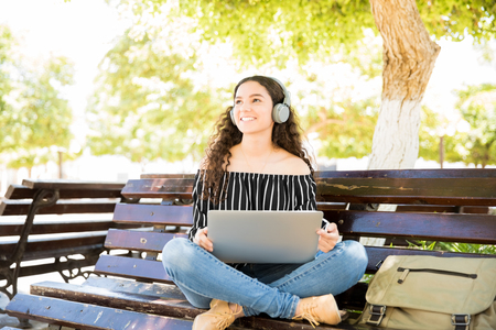 Portrait of beautiful latin teenage girl sitting on park bench with a headphones and laptop computer looking away smiling