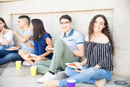 Portrait of beautiful young woman sitting outdoors with friends eating pizza and making eye contact Stock Photo