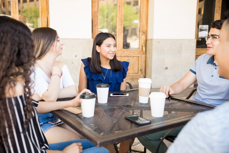 Five young friends sitting at restaurant table having coffee and chatting