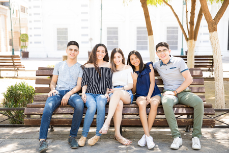 Group of hispanic teenage friends sitting on bench outdoors looking at camera and smiling