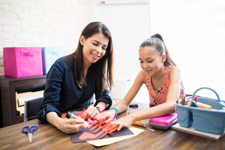 Mid adult mother and daughter gluing paper shape at table in home